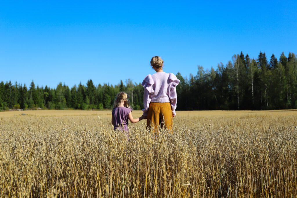 eroakiireesta_Kaisa Karlsson ja lapsi_heinäpelto_Pertunmaa_Mikkelin seutu