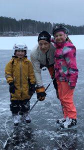 Isä ja lapset pelaa jääkiekkoa. Puumala. Mikkelin seutu.