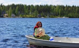 Soutuveneessä Saimaalla. Taustalla asutusalue Puumalan rannalla.